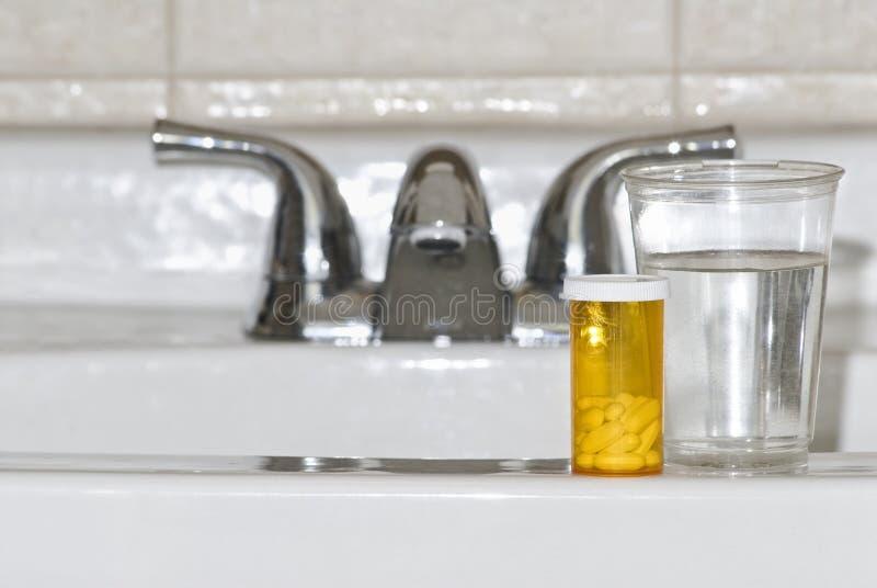 Pillules et eau sur le bassin de salle de bains photo libre de droits