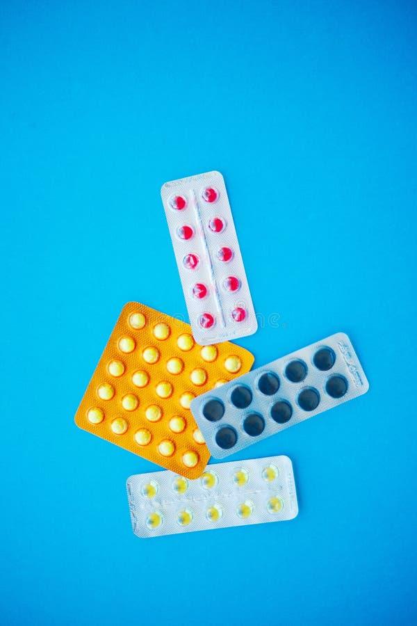 Pillules médicales Pilules et capsule colorées sur le fond bleu Pha photos stock