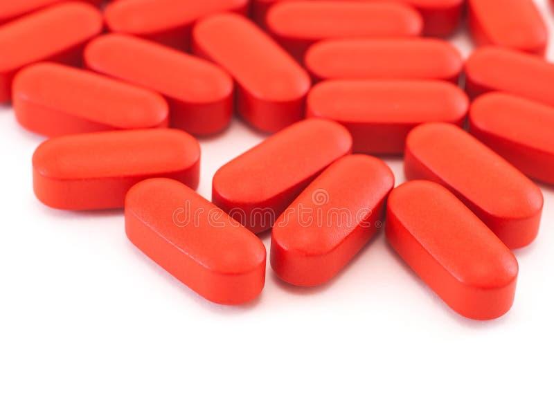 Pillules ovales rouges sur le blanc image stock