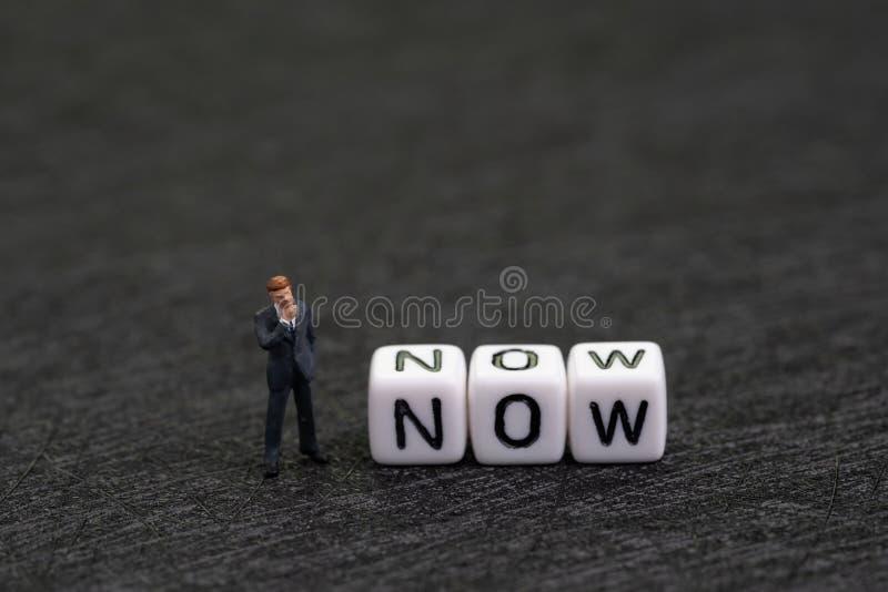 Pilność, przerwa przekłada i dojutrkostwo, motywacji pojęcie, miniatury postaci biznesmena pozycja z białym sześcianem z fotografia stock