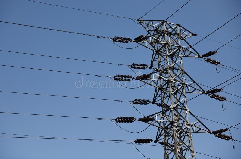 Pilone d'acciaio di elettricità e linee ad alta tensione sopraelevate dell'alimentazione elettrica contro un chiaro cielo blu in  fotografia stock libera da diritti