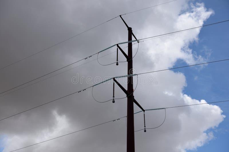 Pilone d'acciaio di elettricità e linee elettriche ad alta tensione contro cielo blu e le nuvole fotografia stock