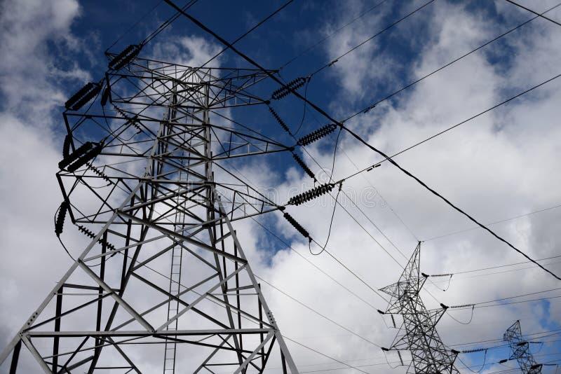 Pilone d'acciaio di elettricit? e linee ad alta tensione sopraelevate dell'alimentazione elettrica contro un cielo blu e le nuvol immagini stock