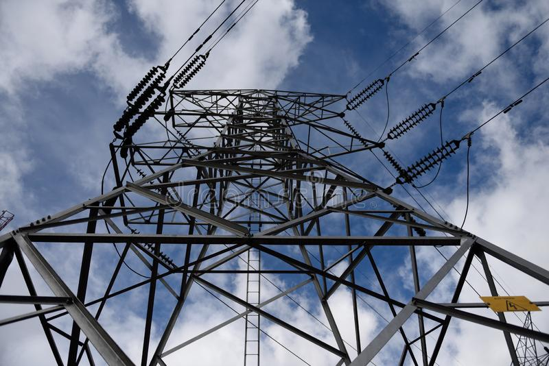 Pilone d'acciaio di elettricit? e linee ad alta tensione sopraelevate dell'alimentazione elettrica contro un cielo blu e le nuvol immagine stock