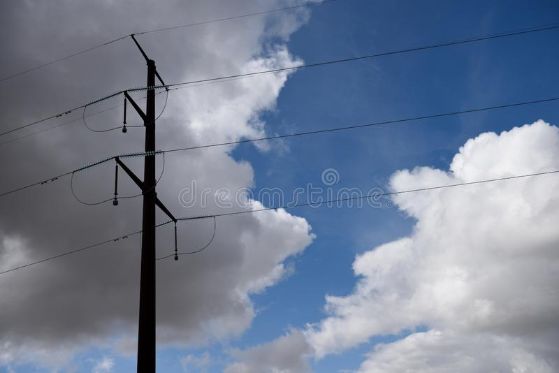 Pilone d'acciaio di elettricit? e linee elettriche ad alta tensione contro cielo blu e le nuvole fotografie stock