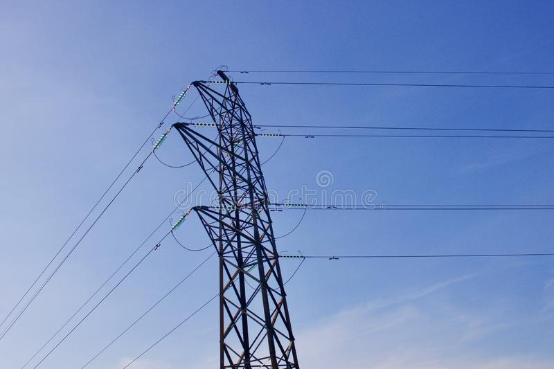 Pilone di elettricit? con i cavi elettrici contro il fondo del cielo blu fotografia stock