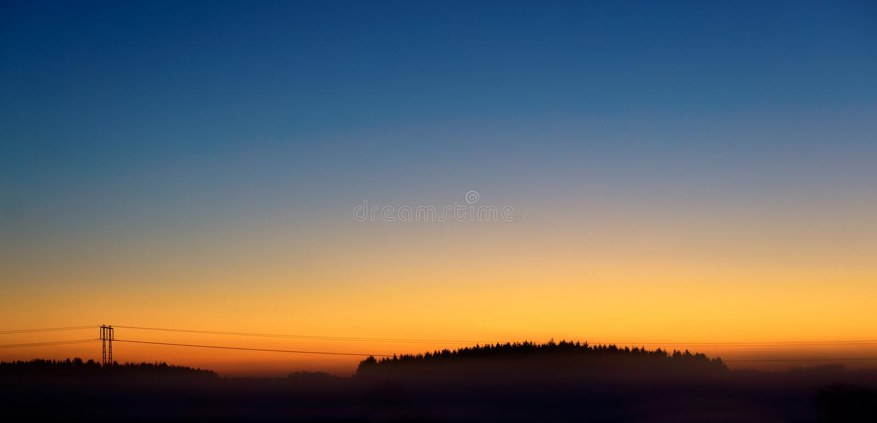 Pilone di elettricità sul cielo arancio fotografia stock