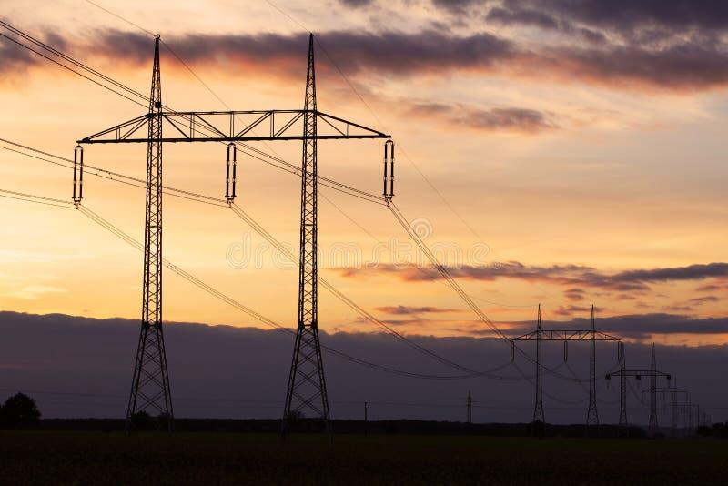 Pilone di elettricità sul tramonto fotografia stock libera da diritti