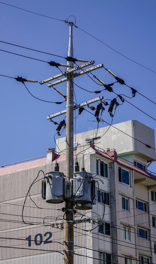 Pilone elettrico del cavo sotto il cielo blu fotografia stock