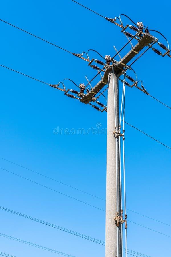 Pilones de alto voltaje con las líneas eléctricas en un campo imagenes de archivo