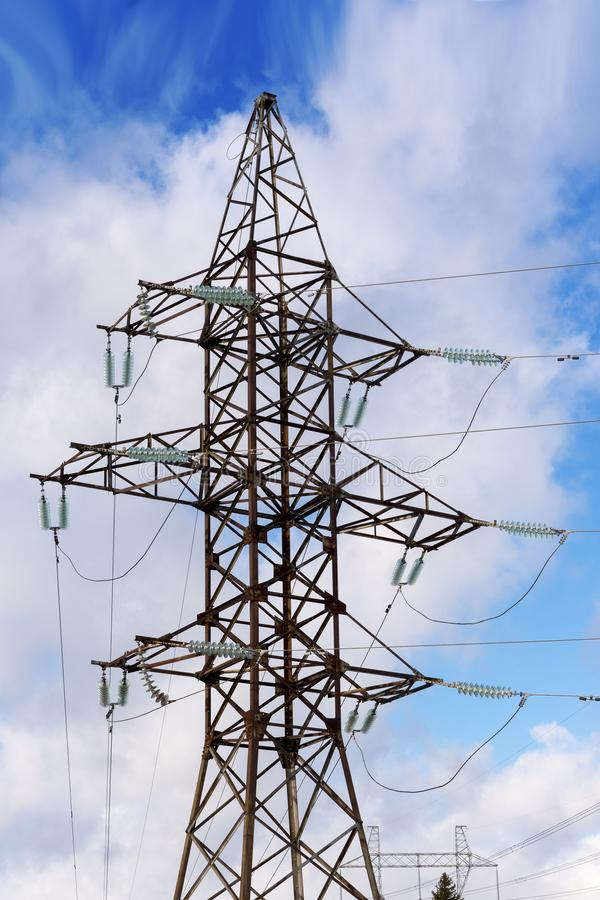 Pilones de líneas eléctricas de alto voltaje y un cielo azul con las nubes foto de archivo libre de regalías