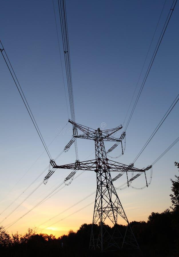 Pilones de la electricidad en la puesta del sol fotos de archivo libres de regalías