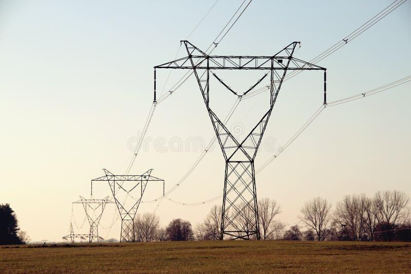 Pilones de la electricidad en la puesta del sol foto de archivo