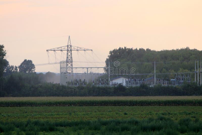 Pilones de la electricidad en la puesta del sol fotografiados fotografía de archivo libre de regalías