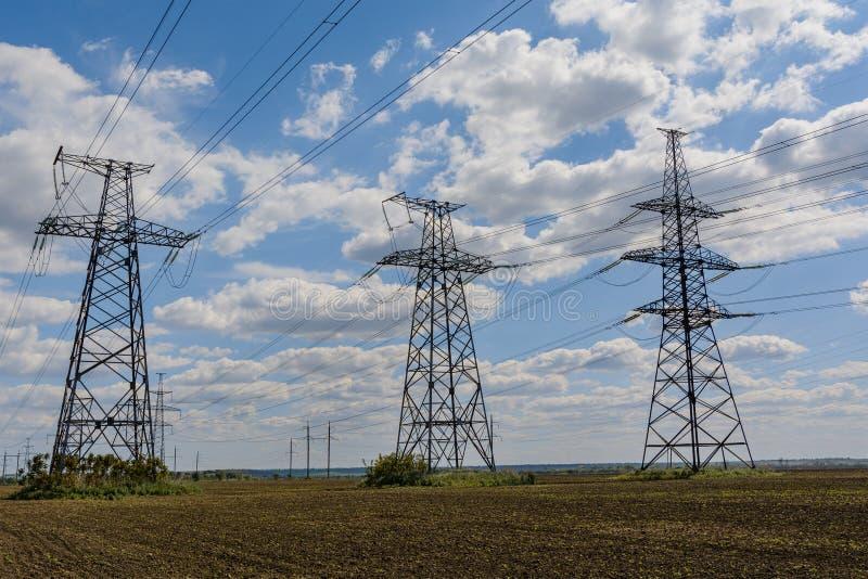 Pilones de la electricidad que entran la distancia sobre campo del verano imagen de archivo