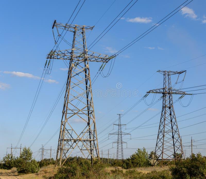 Pilones de la electricidad que entran la distancia sobre campo del verano foto de archivo