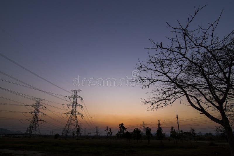 Pilones de la electricidad de la silueta foto de archivo