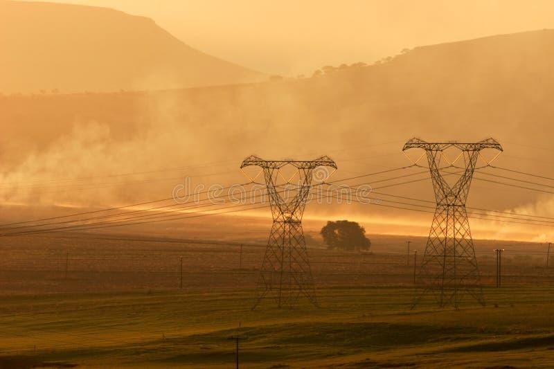 Pilones de la potencia en la puesta del sol imagenes de archivo