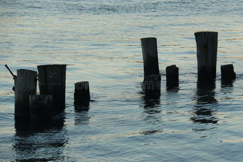 Pilones en agua en la puesta del sol foto de archivo