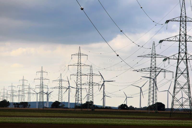 Pilones y granja de viento eléctricos fotografía de archivo libre de regalías