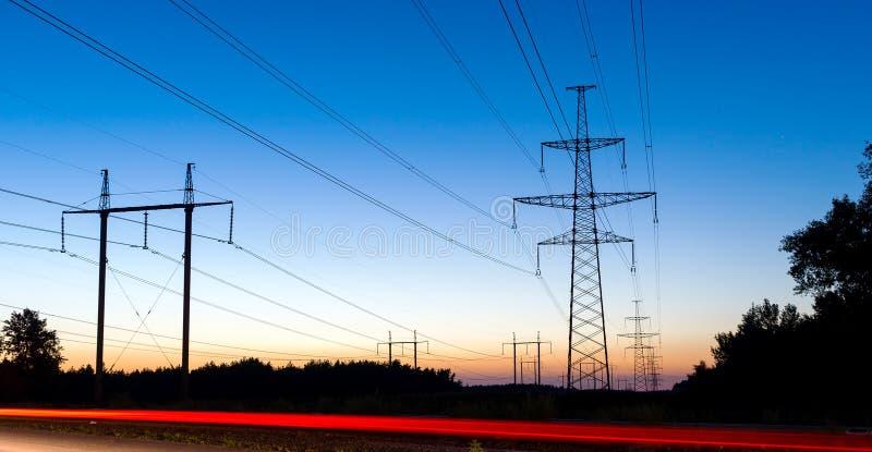 Pilones y líneas eléctricas de la electricidad en la noche con los semáforos imagen de archivo libre de regalías