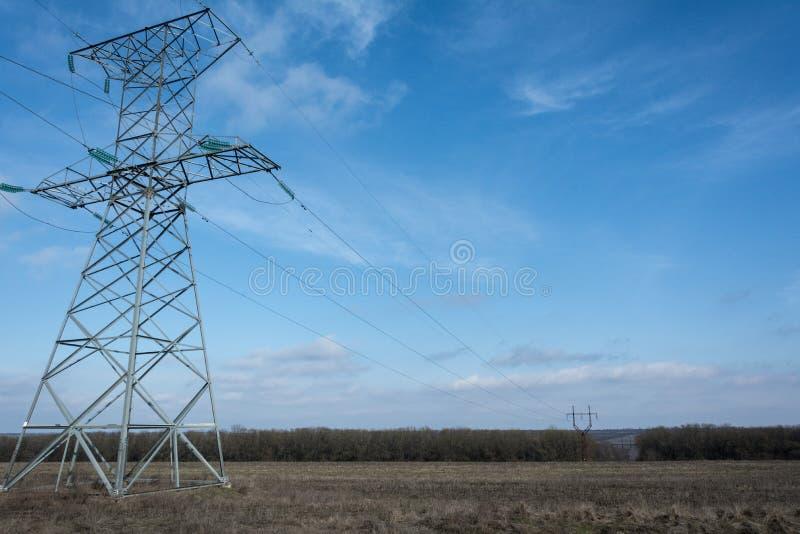 Piloni ad alta tensione contro il cielo blu di inverno immagine stock libera da diritti