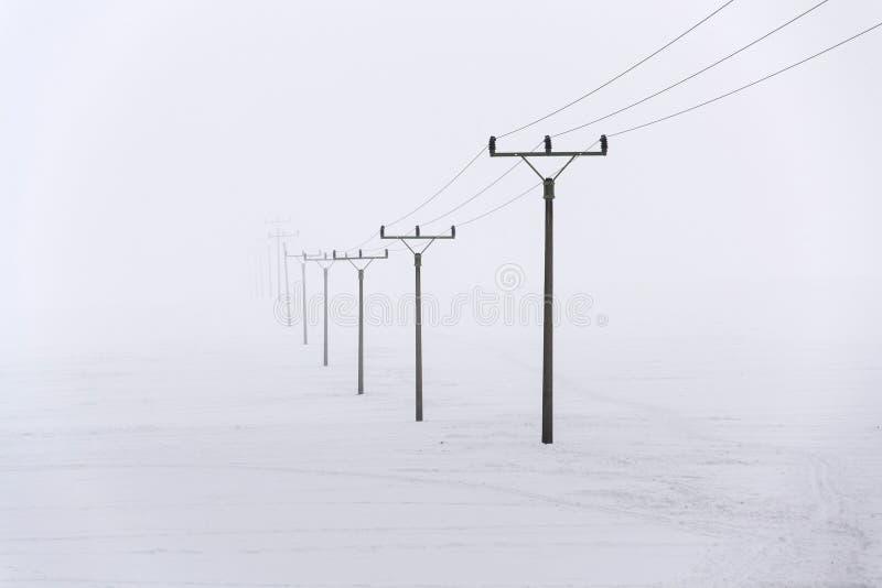 Piloni di elettricità dalla centrale elettrica di distribuzione che scompare in nebbia profonda, tempo di congelamento di inverno immagine stock