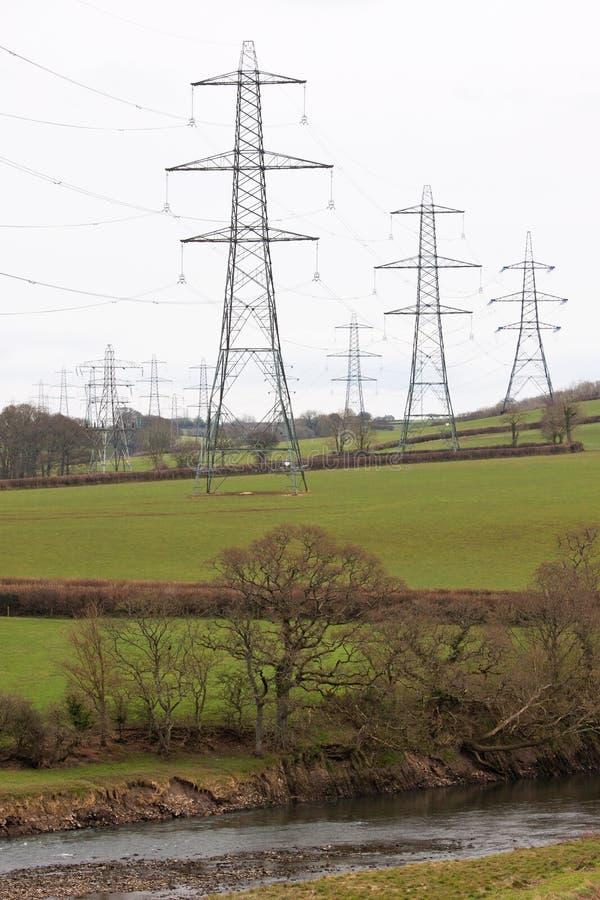 Piloni di elettricità nella campagna BRITANNICA fotografia stock libera da diritti