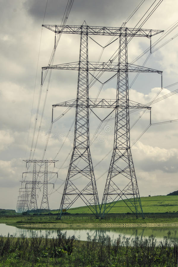 Piloni di elettricità in una fila fotografie stock