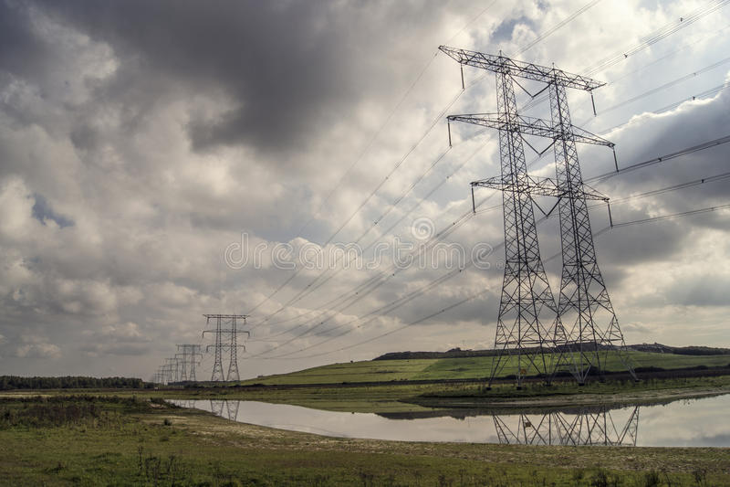 Piloni di elettricità in una fila fotografia stock libera da diritti