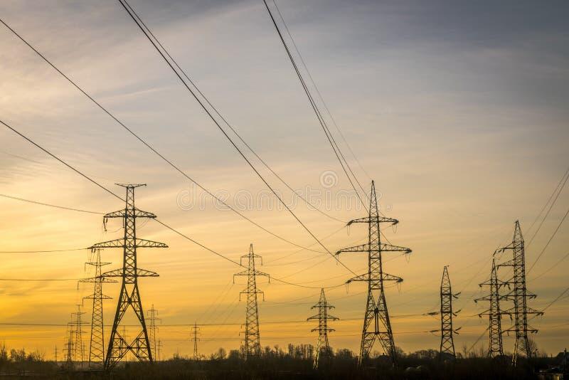Piloni elettrici con le funi ed i cavi all'alba o al crepuscolo fotografia stock libera da diritti