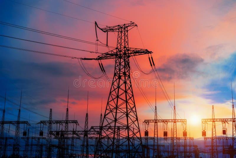 Piloni elettrici sui precedenti della sottostazione del trasformatore durante il tramonto immagine stock