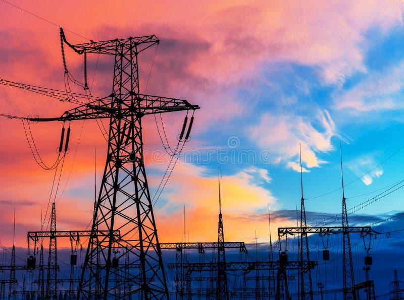 Piloni elettrici sui precedenti della sottostazione del trasformatore durante il tramonto fotografia stock