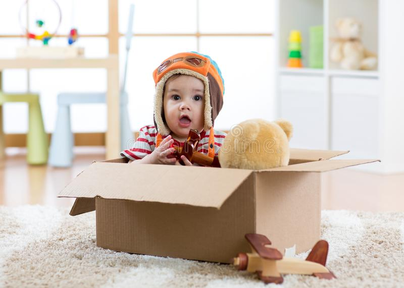 Pilot aviator baby with teddy bear toy and planes plays in cardboard box. Pilot aviator baby boy with teddy bear toy and planes plays in cardboard box royalty free stock images