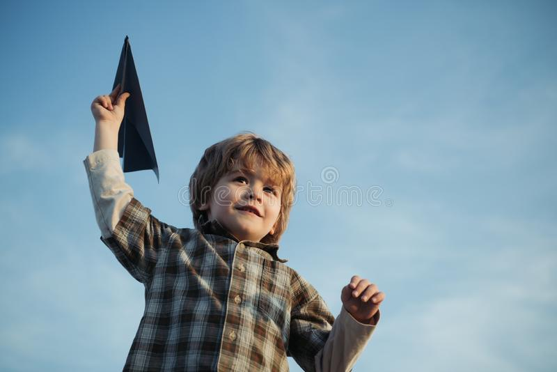Pilot aviator child with a toy airplane plays on summer nature. Child in the village with plane in his hands. Childhood stock photo