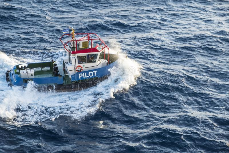 Oranjestad, Aruba - April 10, 2018: Pilot boat guiding cruise ship to the shore #2 royalty free stock images