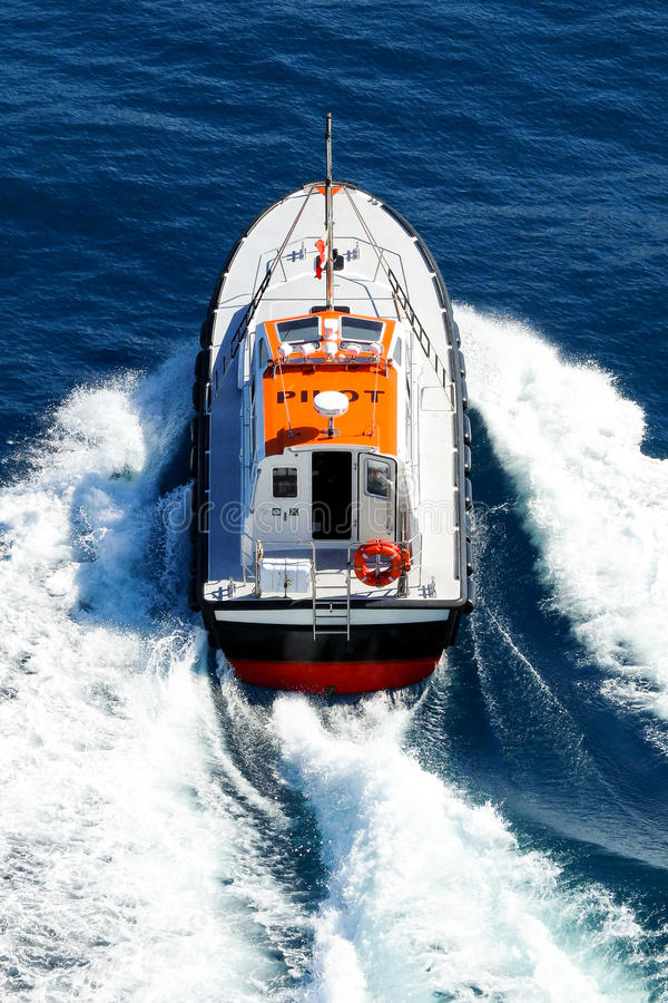 Pilot boat in navigation. A pilot boat powerfully navigates in a blue sea, leaving a big white foam behind it royalty free stock image