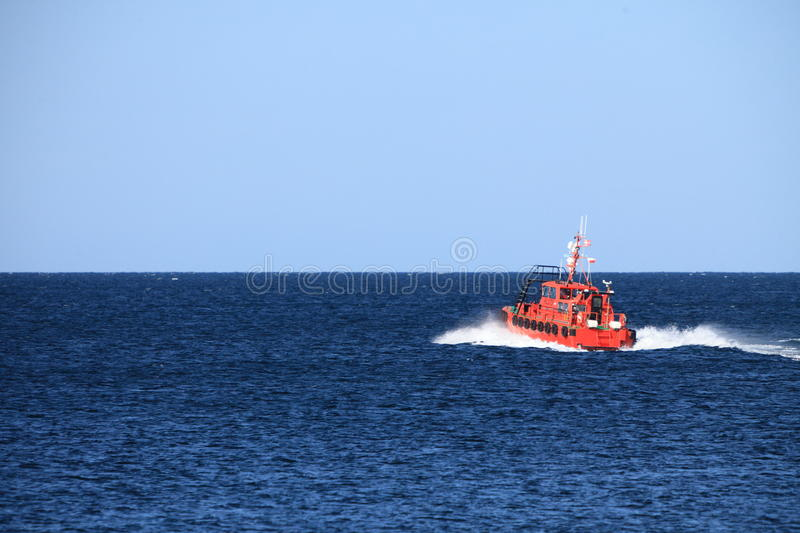 Pilot boat orange tugboat at the sea stock photography