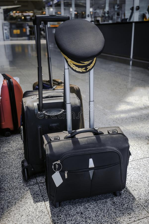 Pilot cap hanging on handle of suitcase at airport stock image