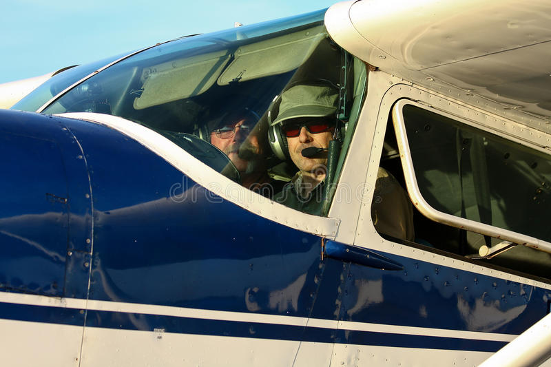 Pilot and co-pilot in cockpit of Cessna 180 stock images