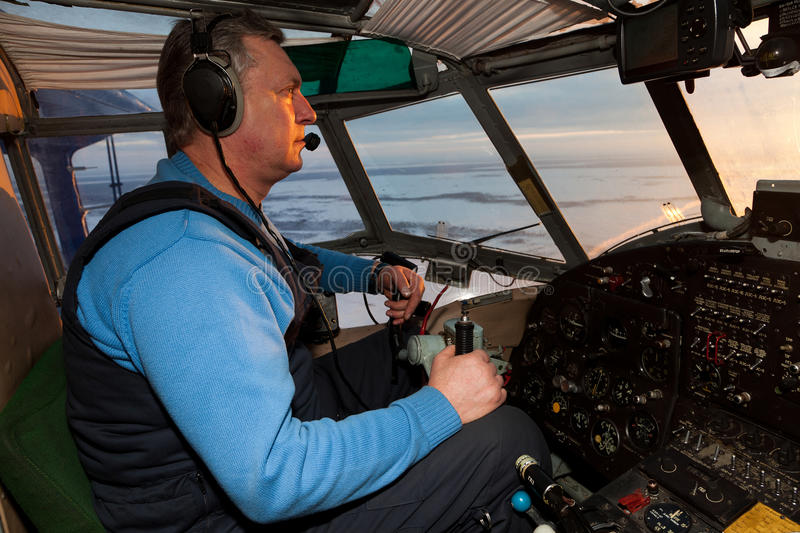 Pilot is controlling the old plane. The pilot in the cockpit of the biplane. He is controlling a visual flight of plane. The plane is flying over winter tundra royalty free stock images