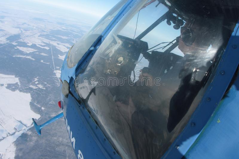 Pilot in the controls of a helicopter flying over the winter earth stock photos
