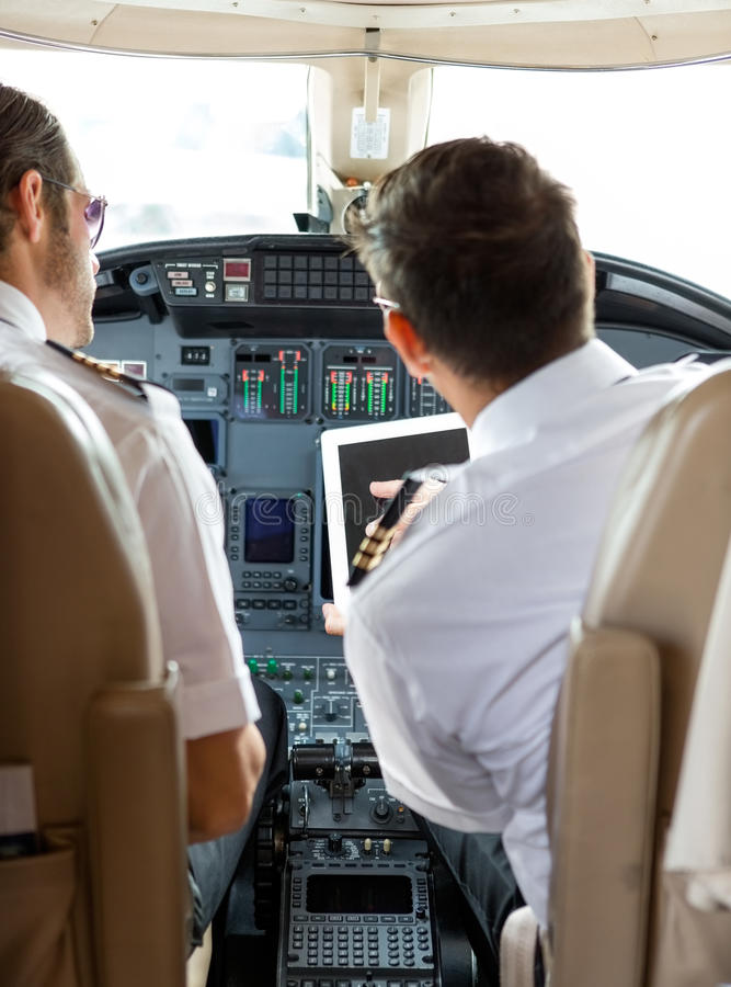 Pilot And Copilot Using Digital Tablet In Cockpit. Rear view of pilot and copilot using digital tablet in cockpit of private jet royalty free stock images