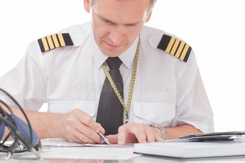 Pilot filling in logbook and checking papers stock photography
