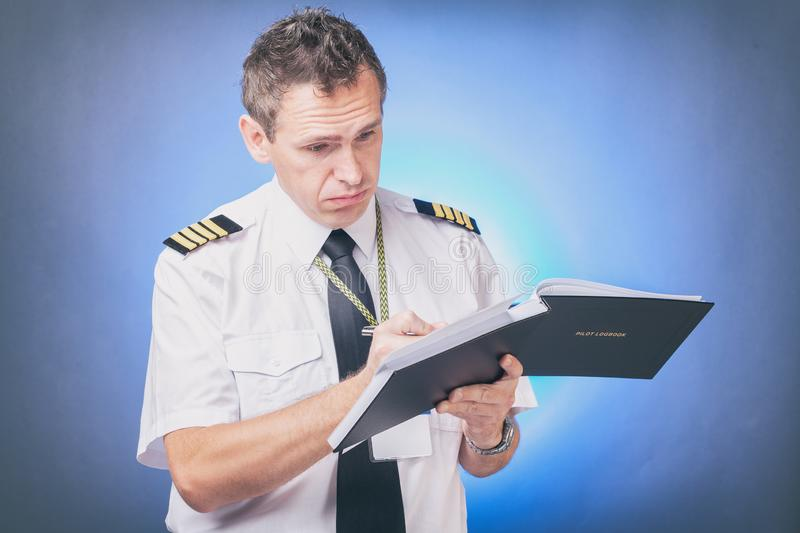Pilot filling in logbook and checking papers royalty free stock photography