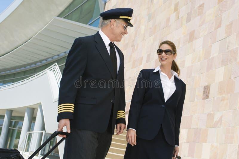 Pilot And Flight Attendant utanför byggnad royaltyfri foto