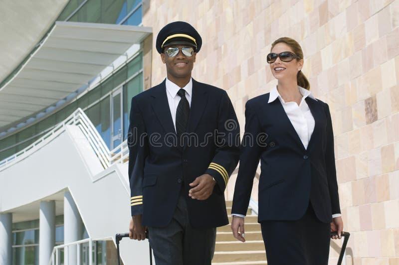 Pilot And Flight Attendant utanför byggnad royaltyfri bild