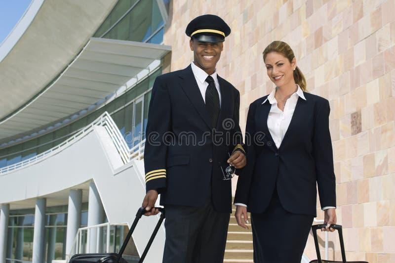 Pilot And Flight Attendant utanför byggnad royaltyfri fotografi