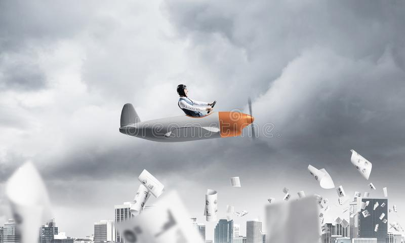 Pilot flying in small paper airplane. Crisis management and control in difficult situation concept. Businessman in aviator hat driving propeller plane in storm stock image