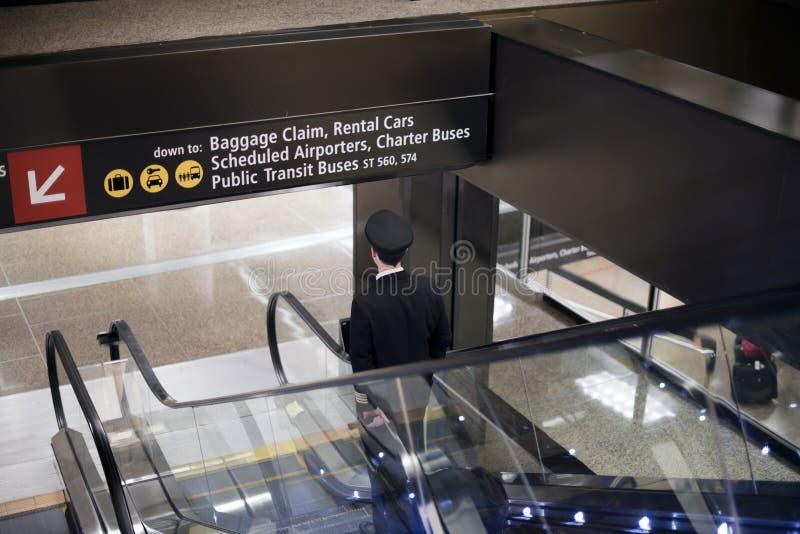 Pilot geht unten mit Koffer auf Flughafenrolltreppe stockfoto